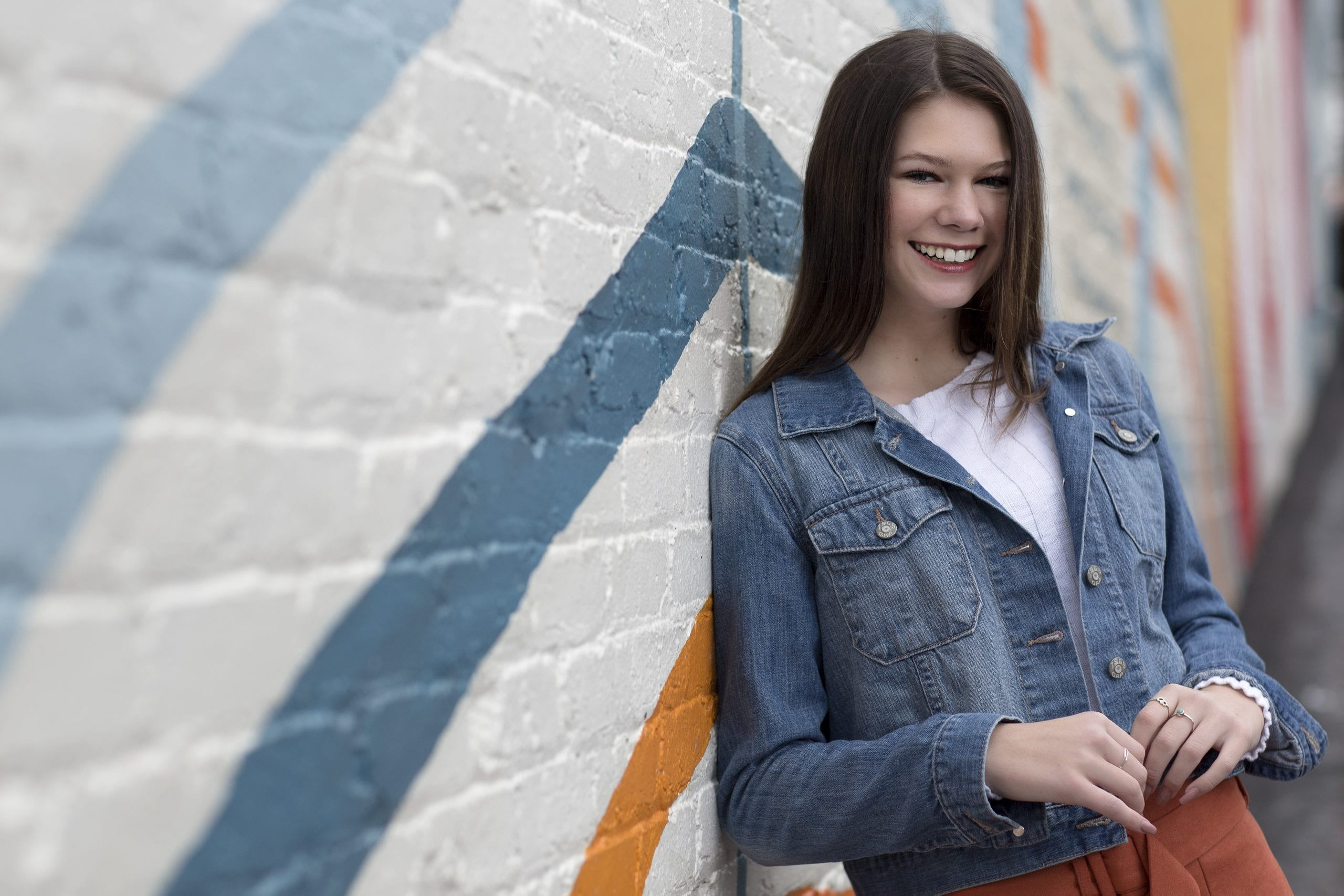 teen in jean jacket leaning against mural
